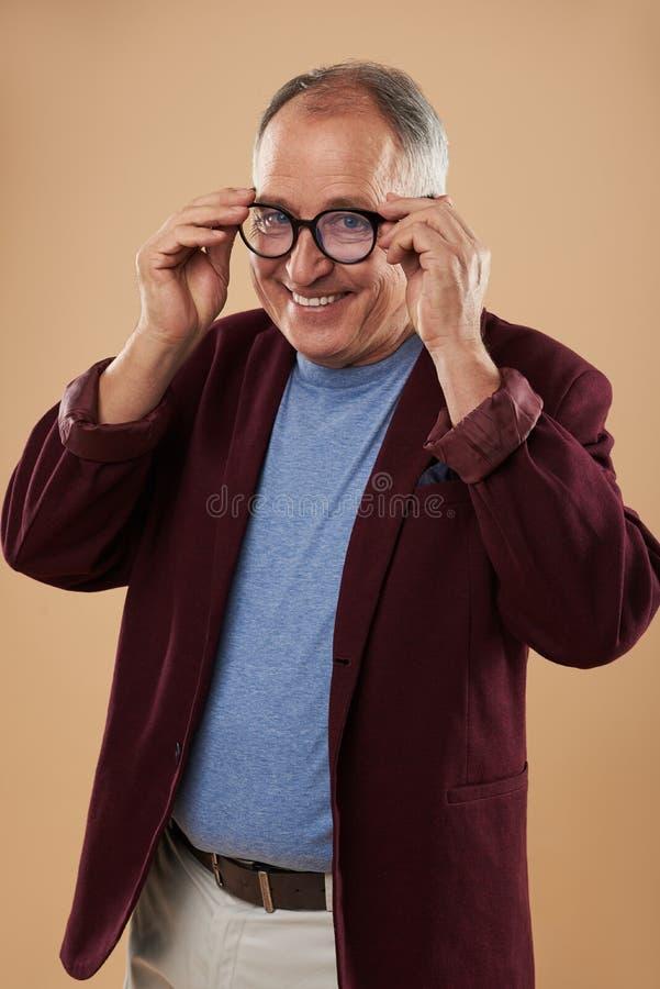 Midja upp av den positiva mannen som bär runda exponeringsglas och att le arkivfoto