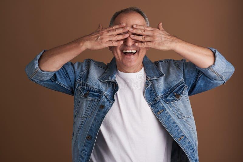 Midja upp av den vuxna mannen som har gyckel och stänger hans ögon arkivbild