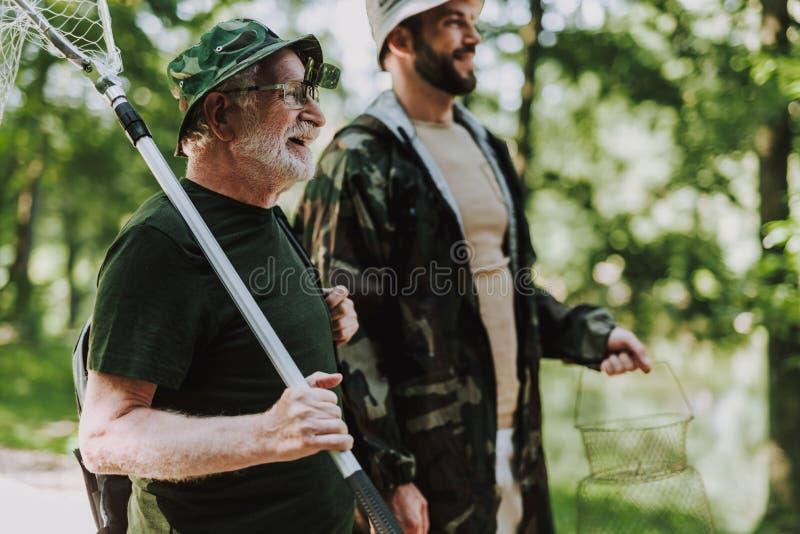 Midja upp av en le man som förbereder sig för att fiska med hans son arkivfoto
