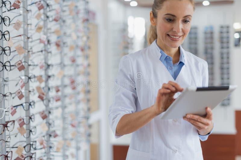 Midja upp av en trevlig optiker som använder hennes minnestavla för arbete arkivfoton