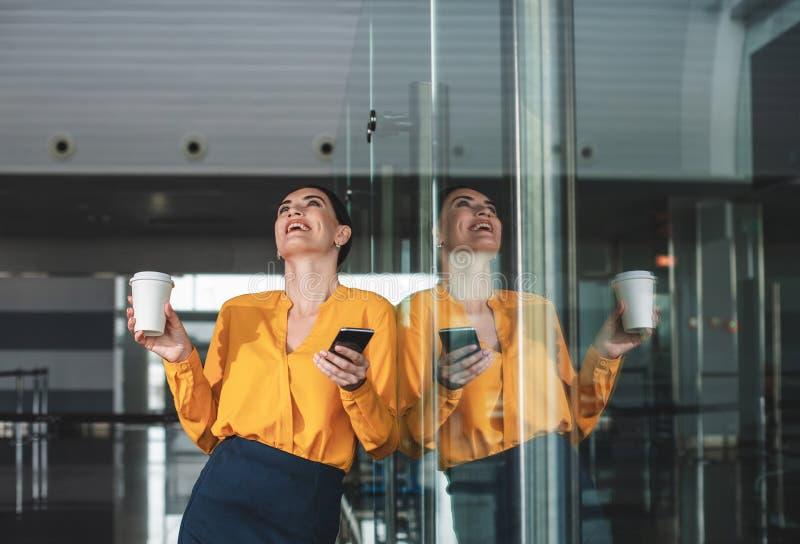 Midja upp ståenden av den gladlynta affärskvinnan nära glasväggen royaltyfri foto