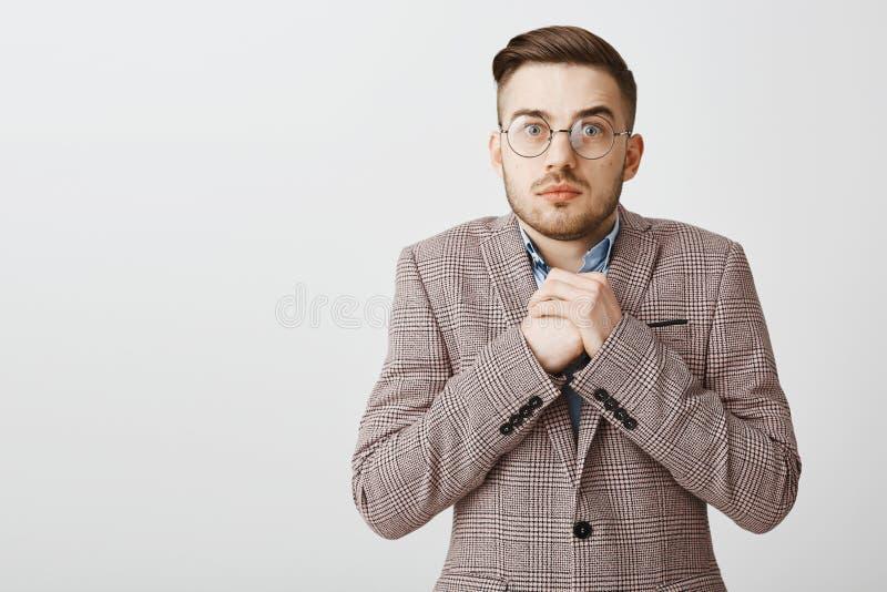 Midja-uppskott av den bekymrade intensiva gulliga europeiska mannen med borstet och kall frisyr i formellt omslag som nära griper royaltyfri bild