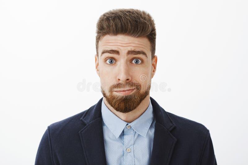 Midja-uppskott av den enfaldiga och dystra gulliga brunettpojkvännen med blåa ögon och smila stå för skägg i elegant dräkt royaltyfri foto