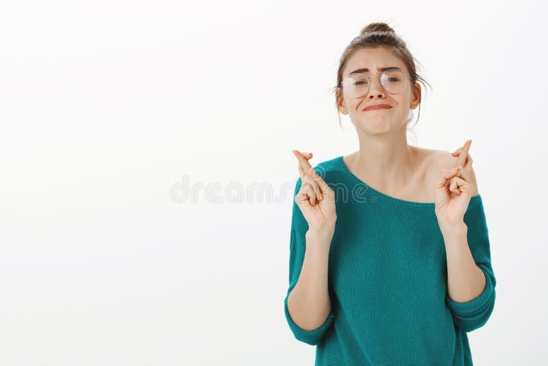 Midja-uppskott av den intensiva bekymrade gulliga europeiska kvinnan i exponeringsglas och lös tröja som börs hakan och nervöst s royaltyfri foto