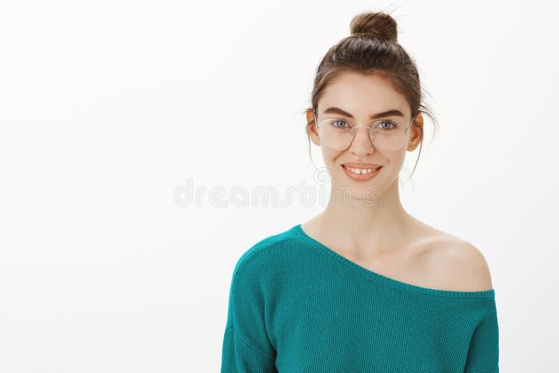 Midja-uppskott av den smarta och idérika gulliga kvinnliga flickan i genomskinliga exponeringsglas med bullefrisyren som i huvuds royaltyfria bilder