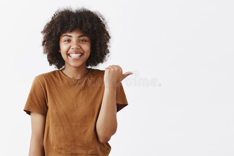 Midja-uppskott av den vänliga snygga optimistiska mörkhyade tonårs- flickan med den afro frisyren i stilfull brun t-skjorta arkivfoto