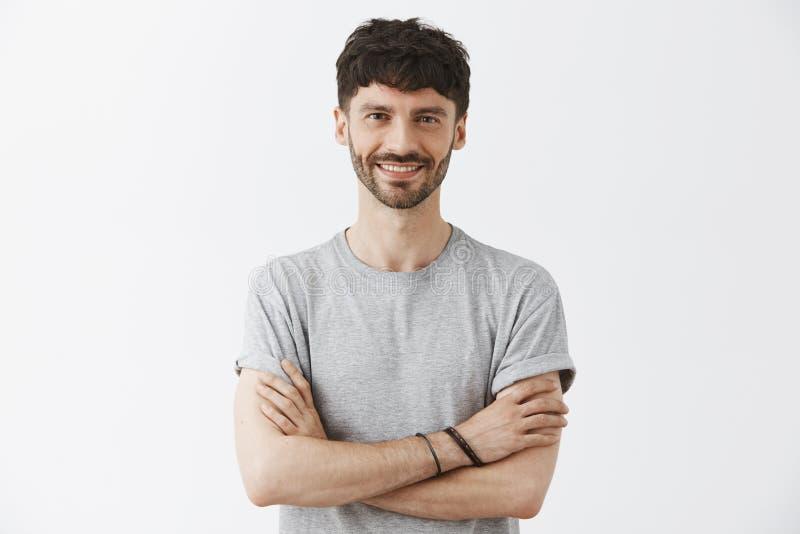 Midja-uppskottet av den säkra snygga mogna europeiska manliga entreprenören i t-skjorta innehavhänder korsade i själv arkivfoto