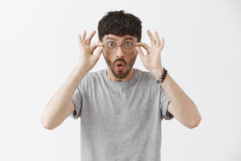 Midja-uppskottet av imponerad och häpen stilig ung manlig programmerare i grå t-skjorta rörande exponeringsglas och att säga över arkivfoto