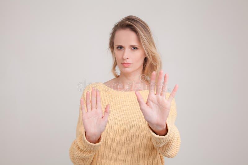 Midja-uppst?ende av den unga blonda kvinnan med missn?jt och ledset framsidauttryck p? framsida och ingen gest som ger avskr?den  royaltyfria foton