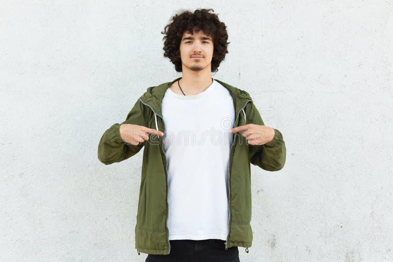 Midjan sköt av stiliga lockiga manpunkter med pekfingrar på den vita t-skjortan, visar upp fritt utrymme för ditt advertizinginne royaltyfri bild