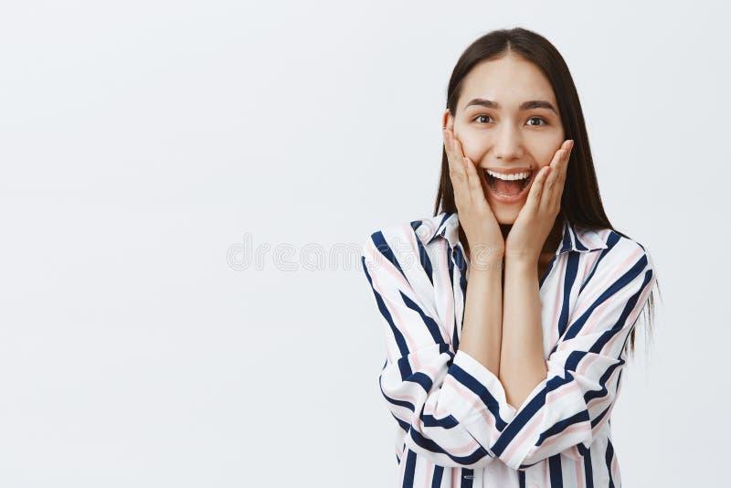 Midjansom skjutas av hänförd lycklig attraktiv mongolian kvinna med långt naturligt mörkt hår och att le i huvudsak som rymmer gö fotografering för bildbyråer