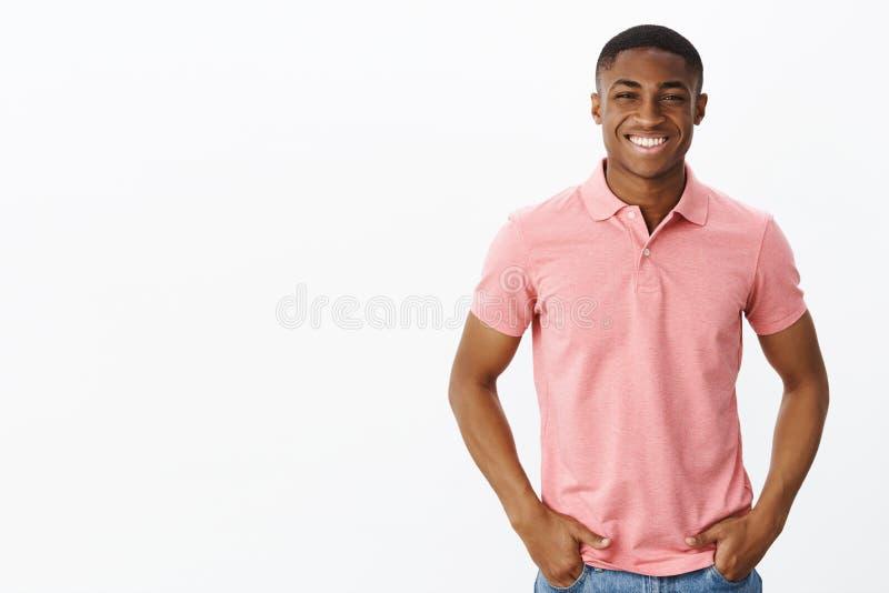 Midjasom skjutas av attraktiv manlig entreprenör för positiv och lycklig ung afrikansk amerikan i den rosa poloskjortan som rymme royaltyfria bilder