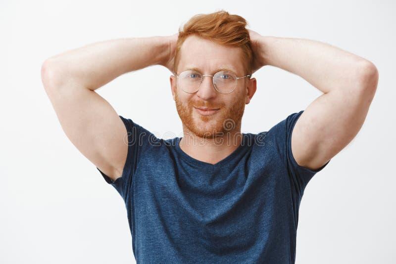 Midjasom skjutas av caucasian grabb för säker och avkopplad manlig rödhårig man i exponeringsglas och blå t-skjorta och att rymma arkivfoton