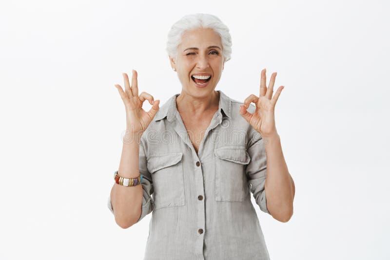 Midjasom skjutas av den karismatiska lyckliga och gulliga enorma farmodern som blinkar joyfully att le och uppvisning av ok geste arkivbild