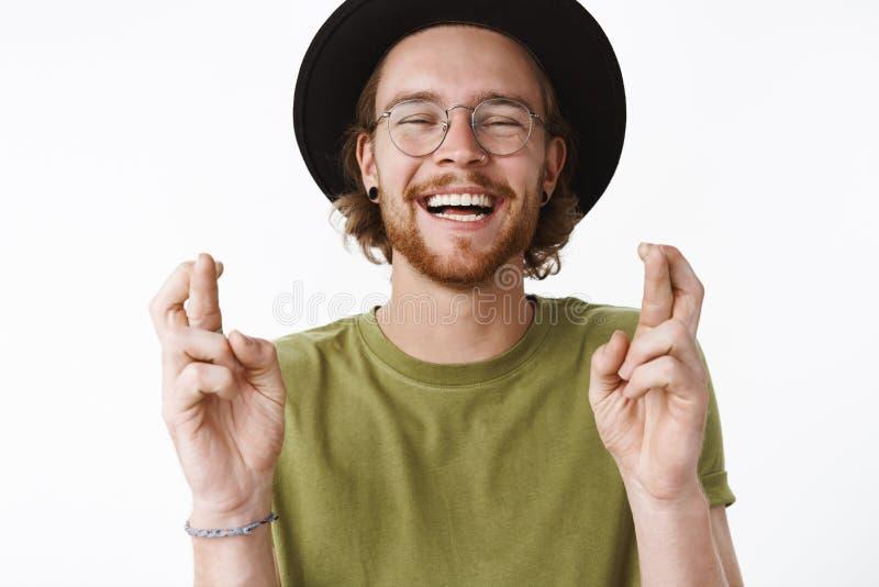 Midjasom skjutas av den optimistiska bekymmerslösa och stiliga unga skäggiga grabben i exponeringsglas och hatt som ut högt skrat royaltyfri foto