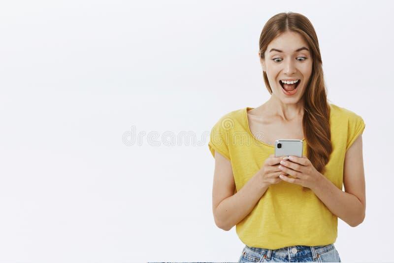 Midjasom skjutas av den roade och upphetsade charmiga caucasian flickan i gul t-skjorta som ler joyfully stirrigt imponerat och royaltyfria bilder