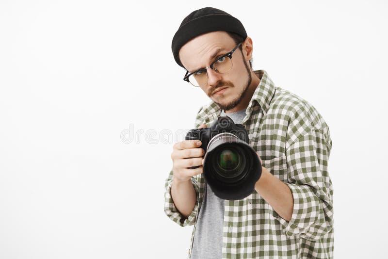 Midjasom skjutas av den roliga allvarlig-seende manliga fotografen i svarta beanieexponeringsglas och kontrollerad skjorta som pe arkivfoton