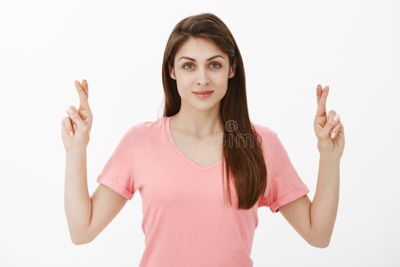 Midjasom skjutas av snygg europeisk kvinnlig modell i rosa t-skjorta och att lyfta korsade fingrar och le på kamerastund royaltyfri bild