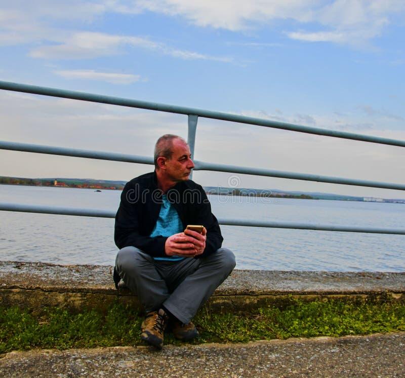 Midle постарело человек сидя на береге озера Человек уединения зрелый используя мобильный телефон на банке Концепция activ стоковая фотография