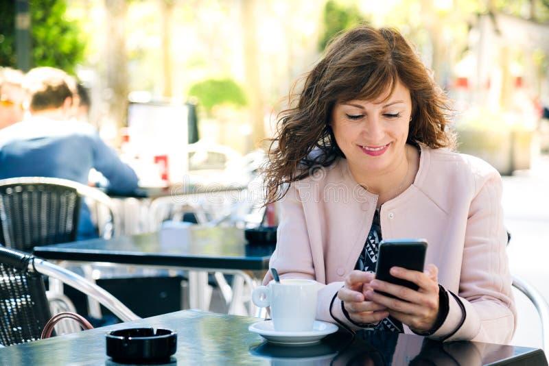 Midle starzał się kobiety używa telefon komórkowego obrazy stock