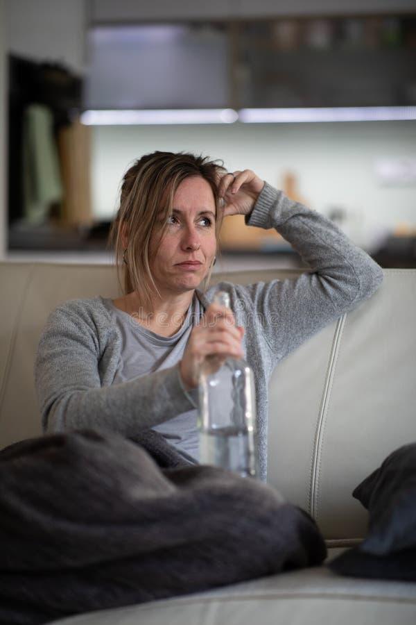 Midlle envelheceu a mulher em casa com uma garrafa do álcool forte imagem de stock royalty free