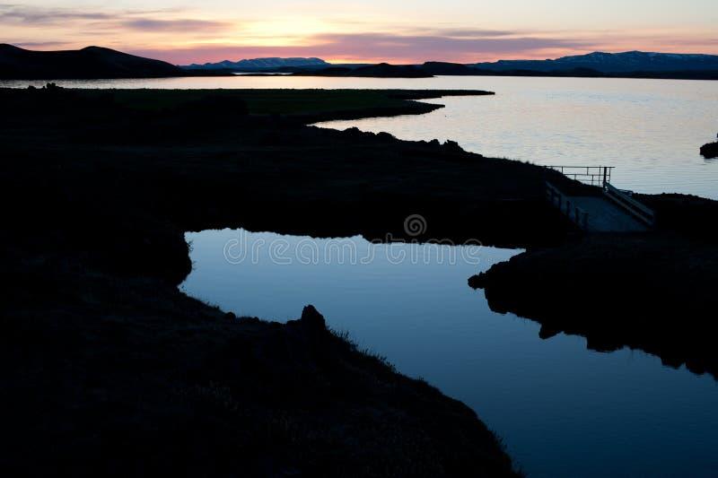 Midnatt sol i Island med sjön Myvatn royaltyfri bild