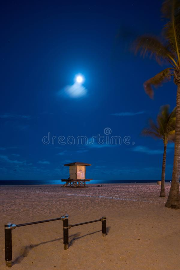 Midnight beach scene with full moon over ocean stock images