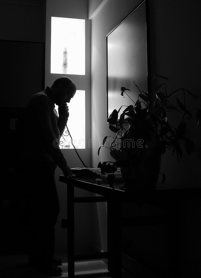 Midnight call -B&W. Young man phoning late at night... - back lit stock image