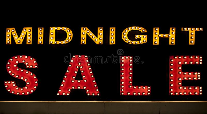 Midnight sale background. Brightly colored vintage advertising sign board with illumination stock image