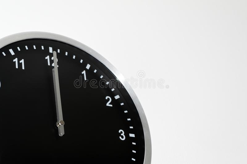 Midnight setting on the black wall clock. With silver colored edge stock image