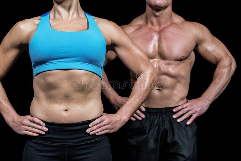 Midsection της μυϊκών γυναίκας και του άνδρα που στέκονται με τα χέρια στο ισχίο στοκ φωτογραφία με δικαίωμα ελεύθερης χρήσης