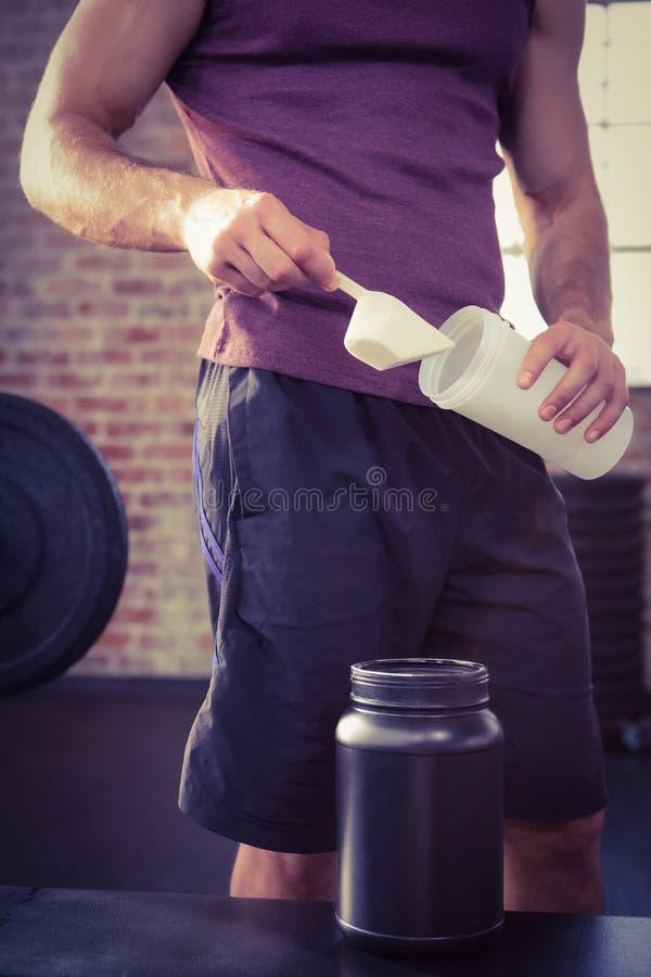 Midsection του ατόμου που βάζει το συμπλήρωμα στο μπουκάλι στοκ φωτογραφία με δικαίωμα ελεύθερης χρήσης