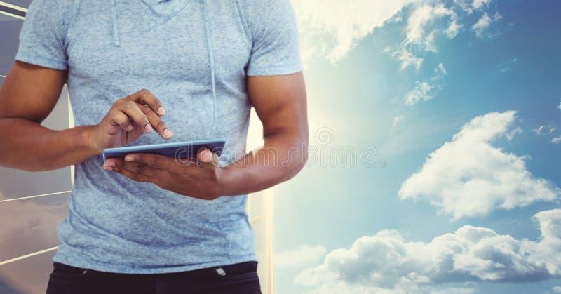 Midsection του ατόμου που χρησιμοποιεί το PC ταμπλετών ενάντια στον ουρανό στοκ φωτογραφία