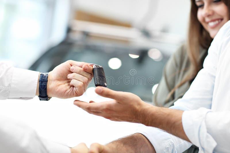 Midsection του νέου ζεύγους που αγοράζει το νέο αυτοκίνητο στοκ φωτογραφία