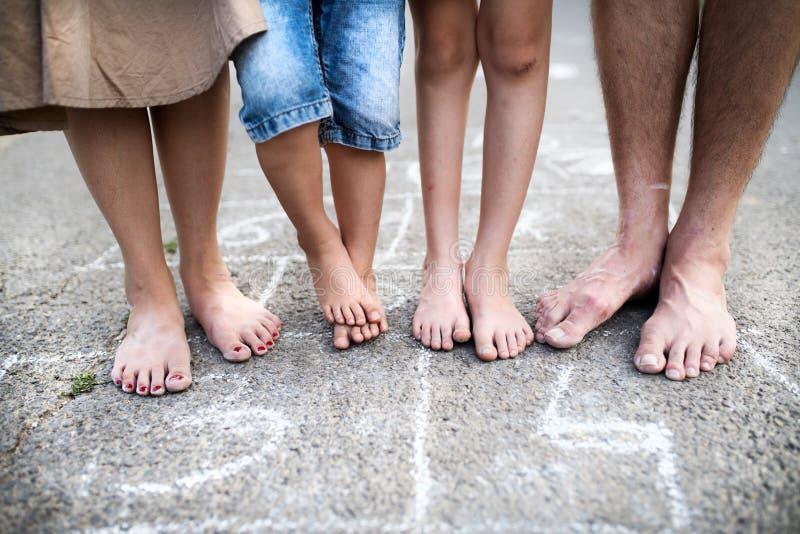 Midsection των ποδιών της οικογένειας με δύο μικρούς γιους που στέκονται χωρίς παπούτσια σε έναν δρόμο στοκ φωτογραφίες