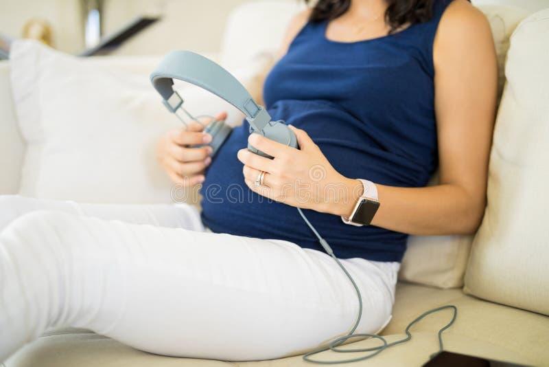 Midsection беременной женщины играя музыку для плода стоковая фотография rf