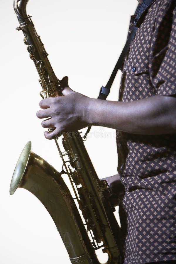 Midsection взгляда со стороны крупного плана человека с саксофоном стоковое изображение