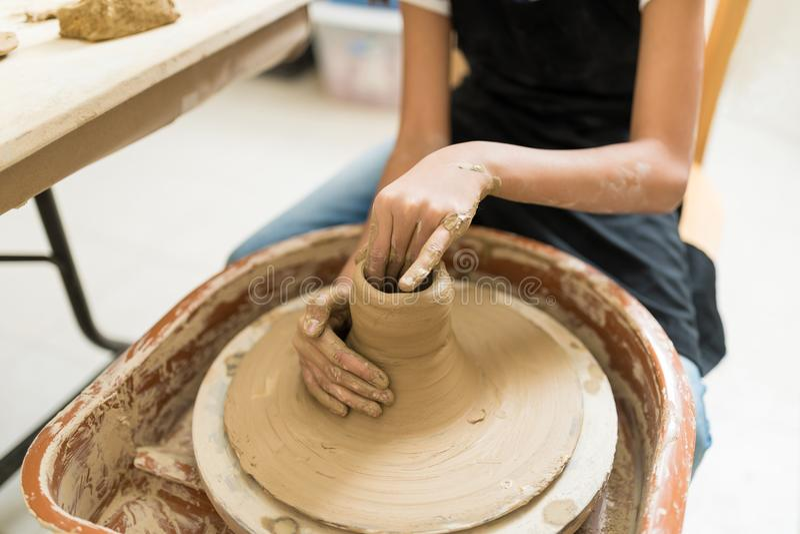 Midsection девушки делая глиняные горшки на колесе гончара стоковая фотография