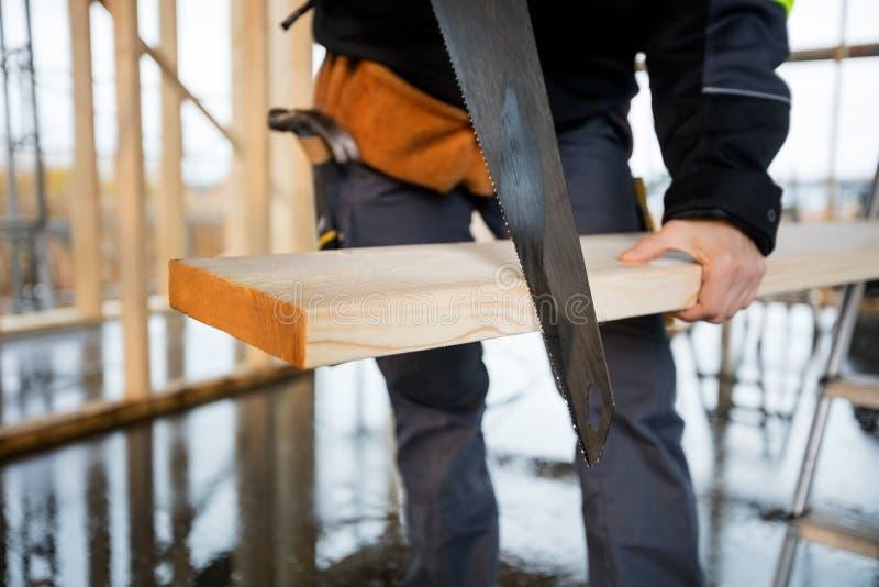 Midsection женского использования плотника увидел для того чтобы отрезать планку стоковое изображение rf