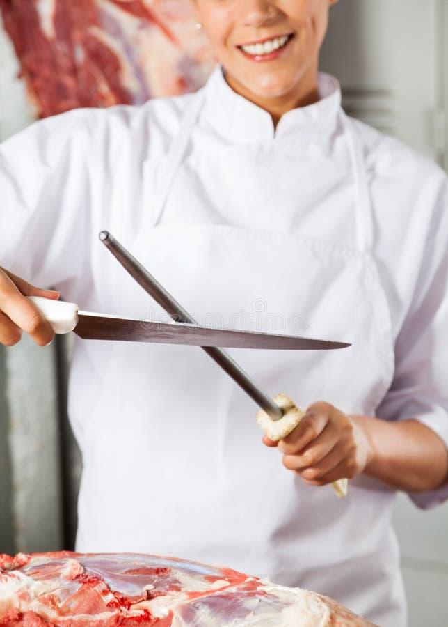Midsection женского мясника точить нож стоковое изображение