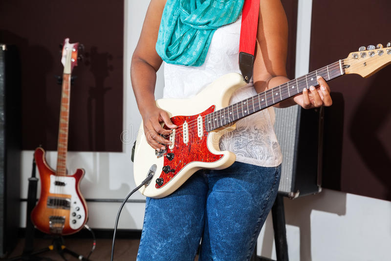 Midsection женского совершителя играя гитару стоковые изображения