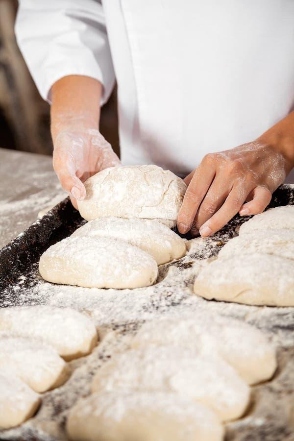 Midsection женщины держа тесто хлеба в подносе выпечки стоковые фотографии rf