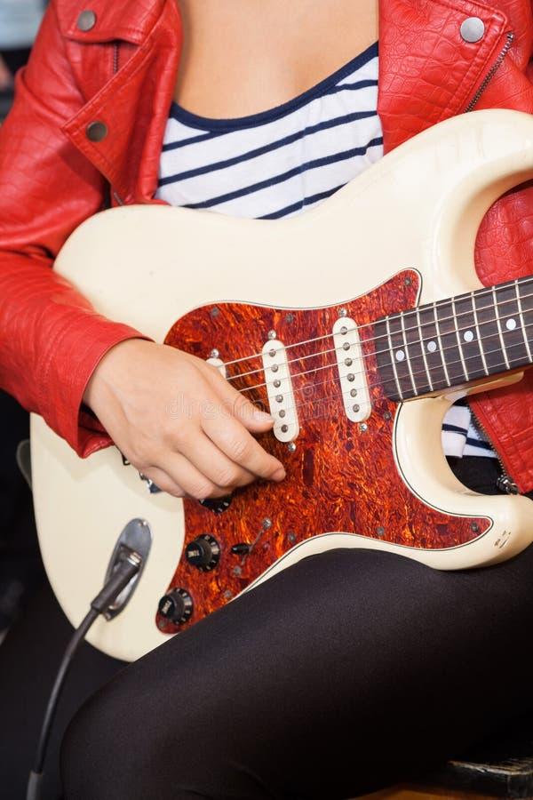 Midsection женщины играя электрическую гитару стоковое фото rf
