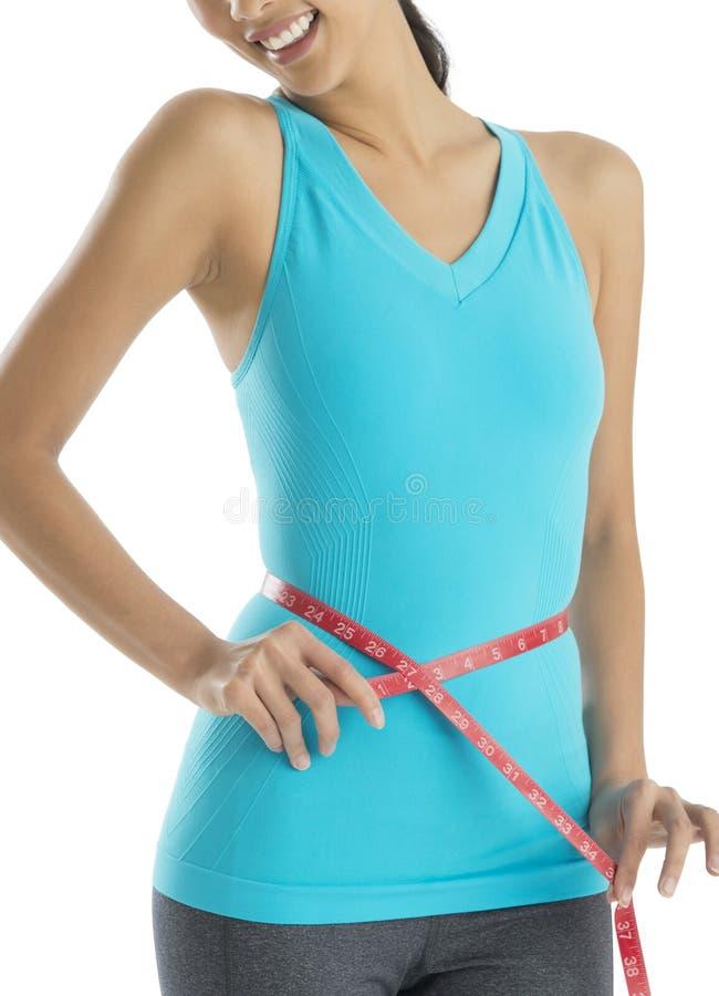 Midsection женщины пригонки измеряя ее талию стоковая фотография rf