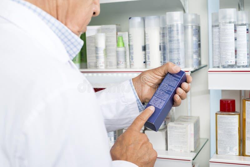 Midsection инструкций чтения аптекаря на коробке медицины стоковые фотографии rf