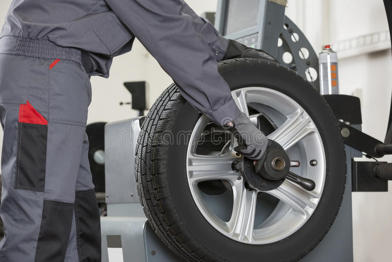 Midsection мужского механика ремонтируя автомобиль катит внутри ремонтную мастерскую стоковые фото