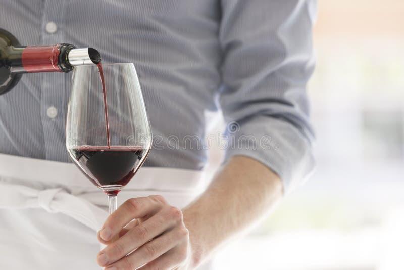 Midsection официанта лить красное вино в рюмке на ресторане стоковое изображение rf