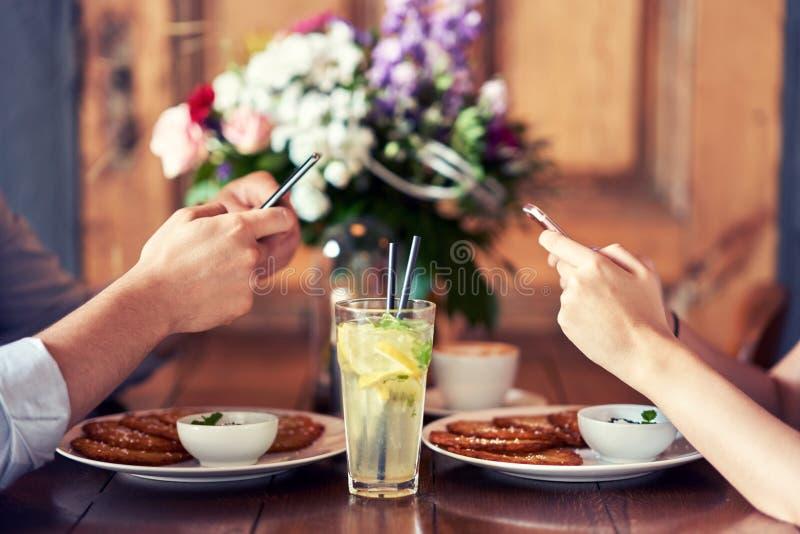 Midsection пар отправляя SMS в ресторане стоковое изображение