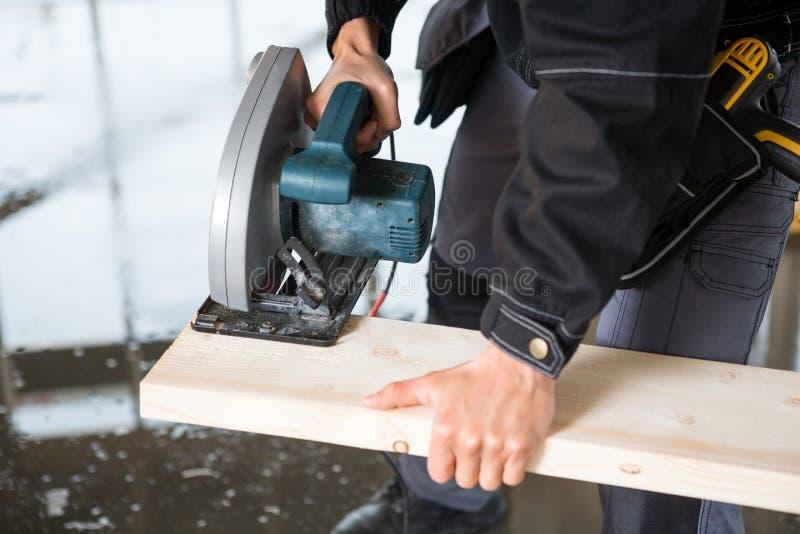 Midsection плотника используя электрический увидел для того чтобы отрезать древесину стоковая фотография
