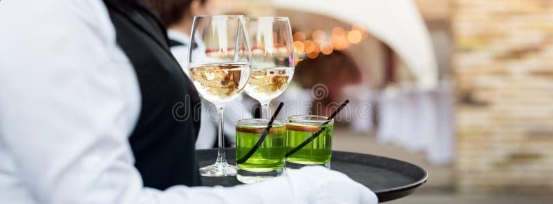 Midsection профессионального кельнера в равномерном вине сервировки во время партии ресторанного обслуживании шведского стола, пр стоковое изображение